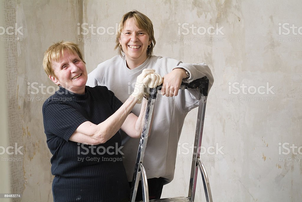 Two smiling women taking a break from painting a room. royalty-free stock photo