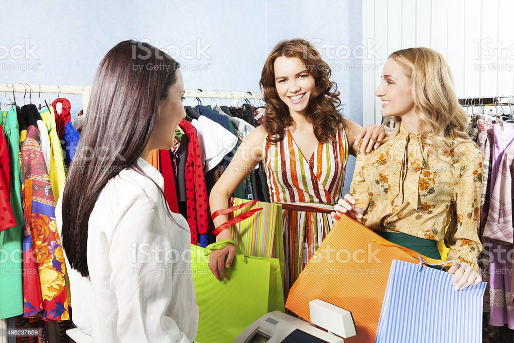 Two smiling women talking with shop assistant stock photo