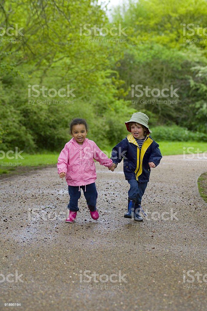 Two Smiling Young Children Running Through The Park royalty-free stock photo
