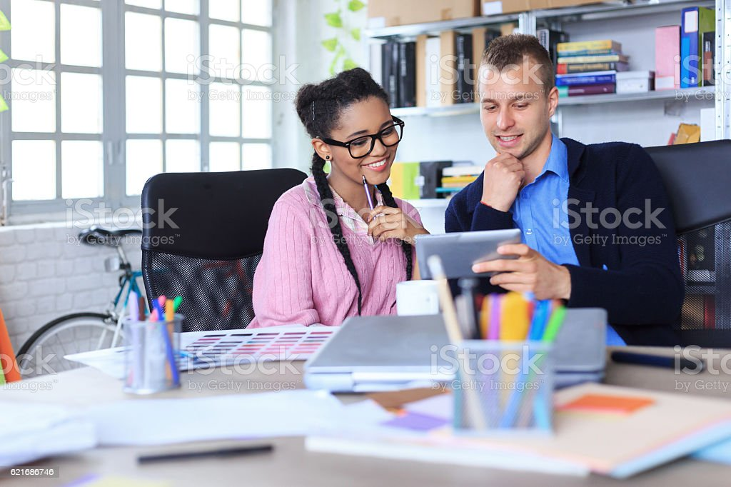 Two smiling young coworkers using digital tablet in the office stock photo