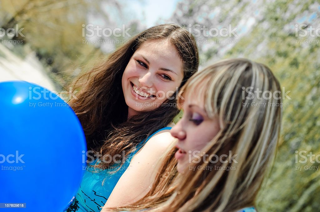 Two smiling young girls with blue balloon stock photo