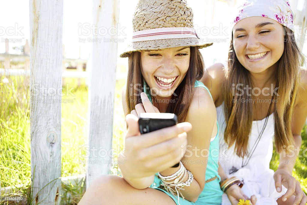 Two smiling young women looking at a smartphone royalty-free stock photo