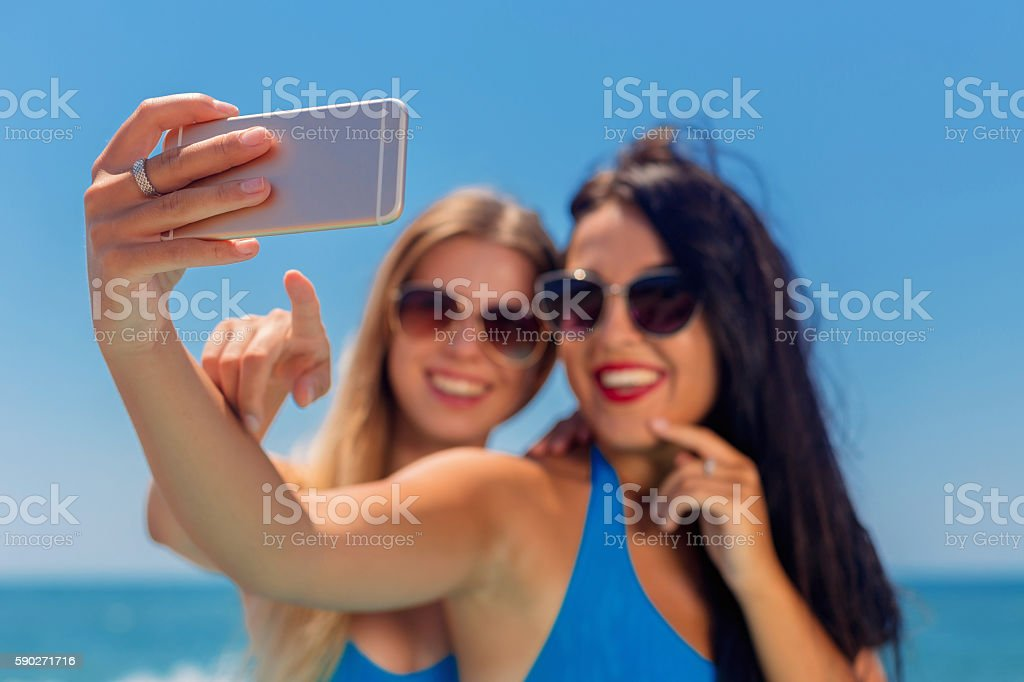 Two smiling young women on beach making selfie stock photo