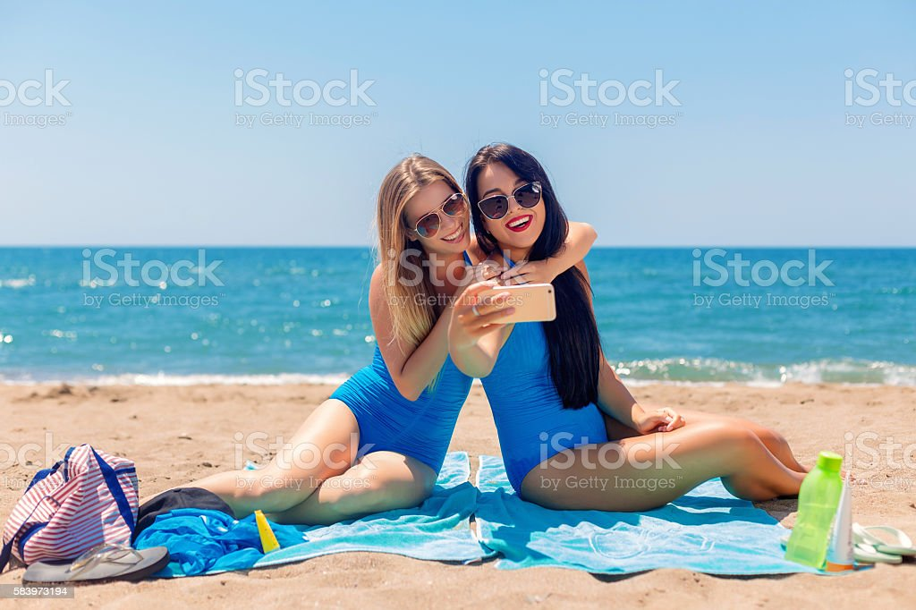 Two smiling young women on beach making selfie with smartphone stock photo
