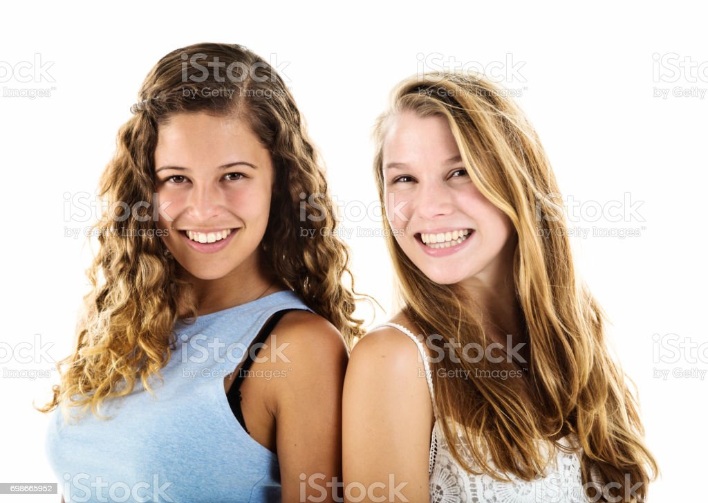 Two smiling young women standing back to back stock photo