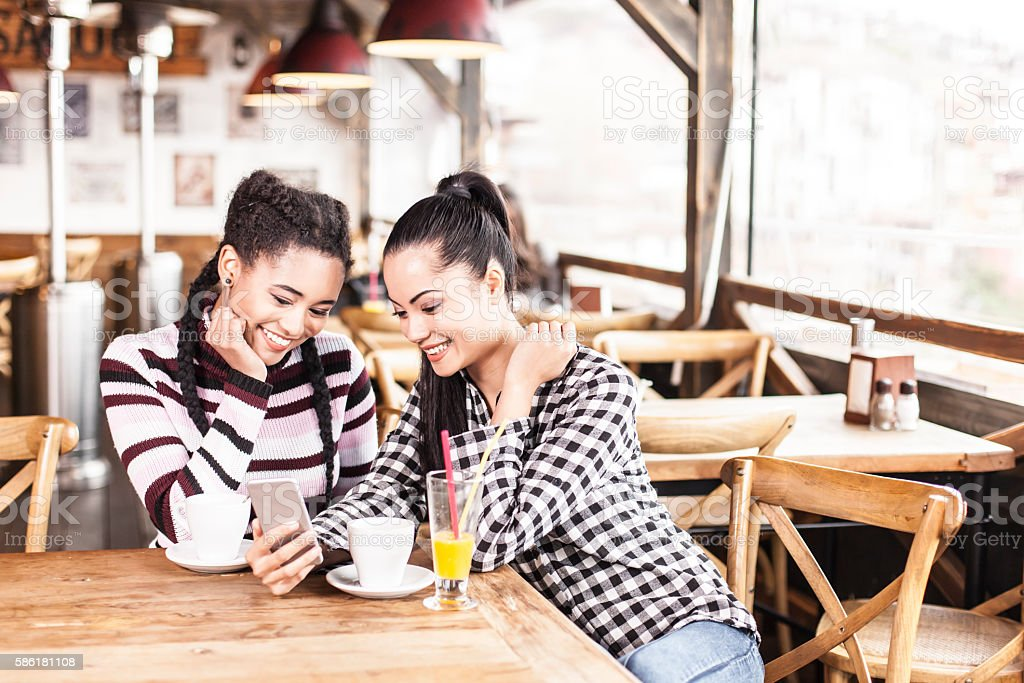 Two smiling young women using smart phone at coffee shop stock photo