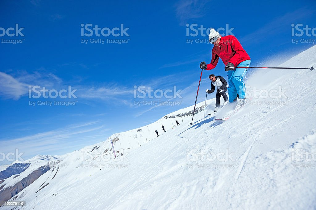 Two Snow Skiers Skiing in the snowy Alps stock photo