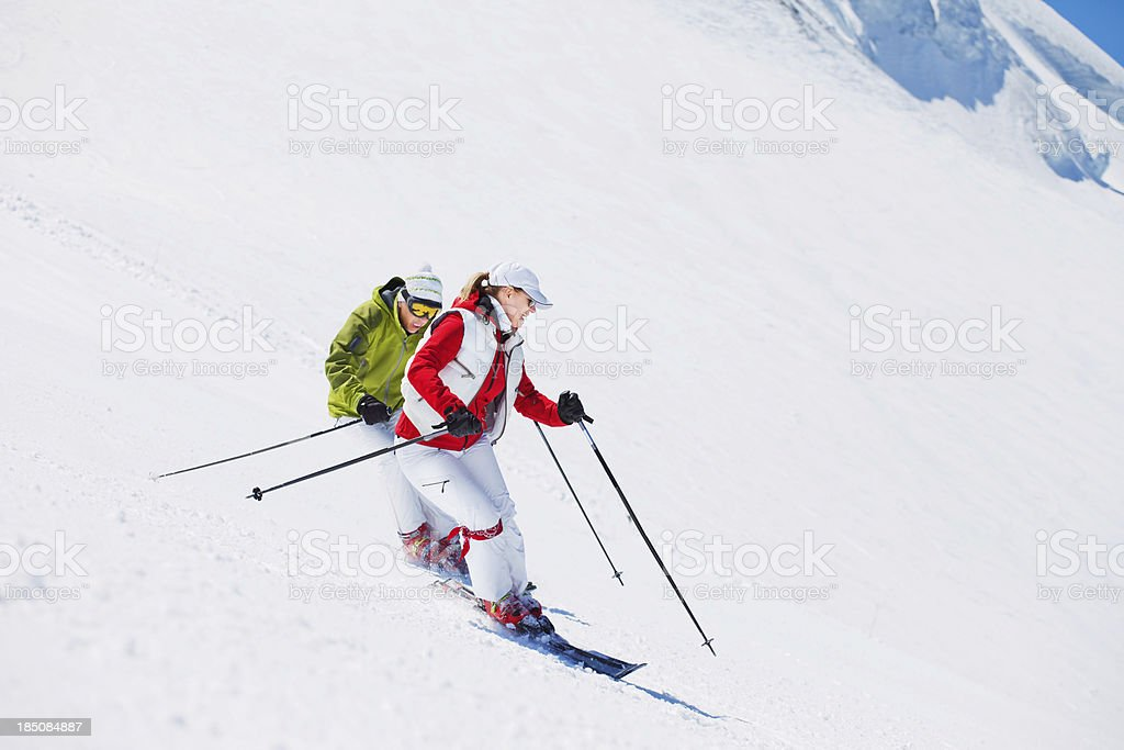 Two Snow Skiers Skiing Parallel in the snowy Alps stock photo