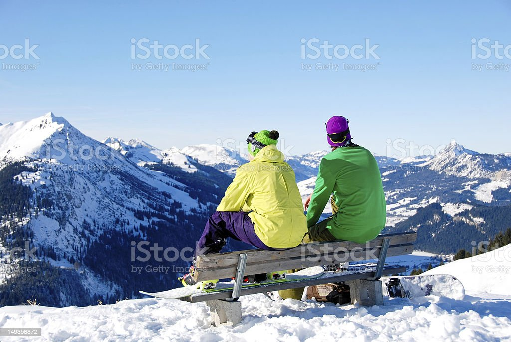 Two snowboard friends sitting on bench in snowy alps royalty-free stock photo