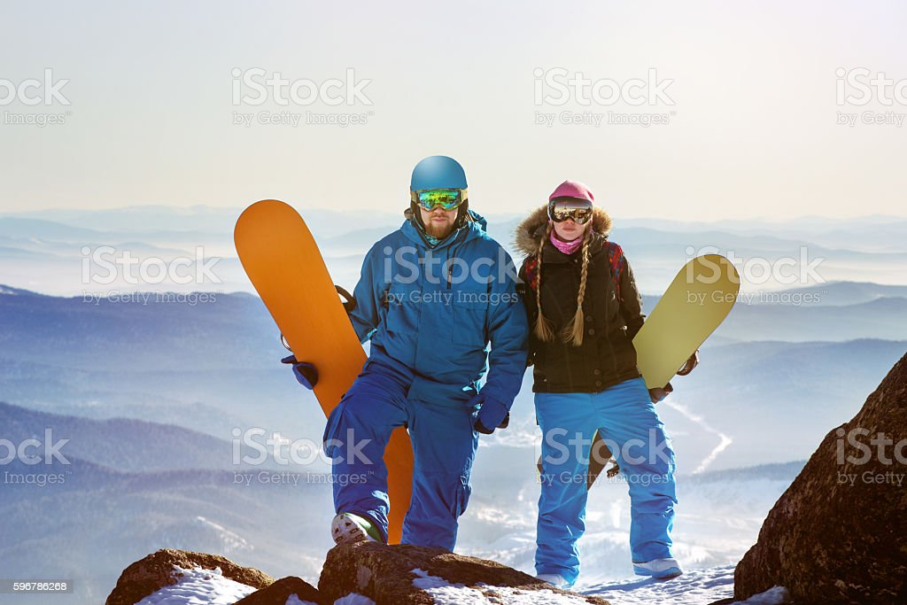 Two snowboarders stands on the top of mountain stock photo
