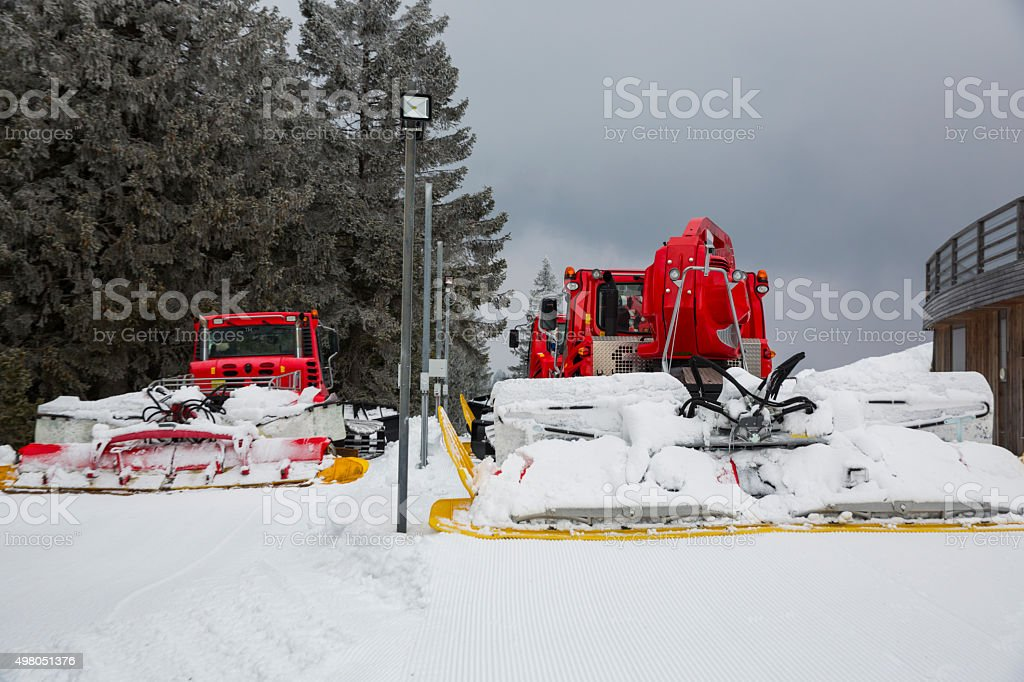 Two snowcats parked after fixing snow on ski slope stock photo