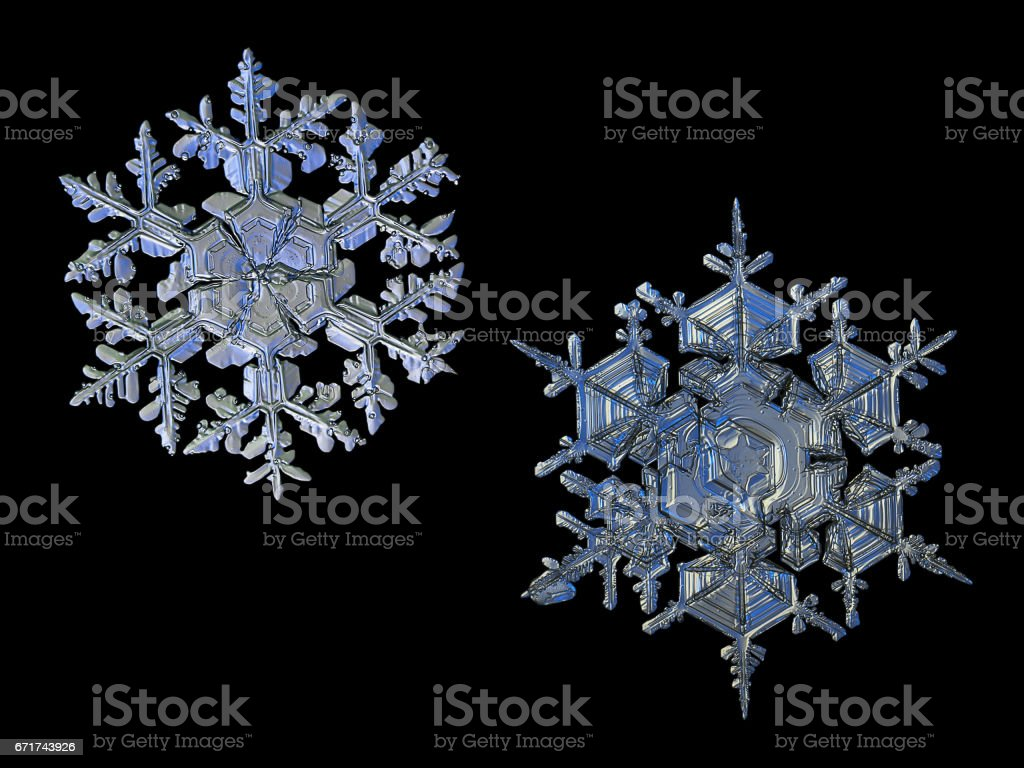 Two snowflakes isolated on black background stock photo