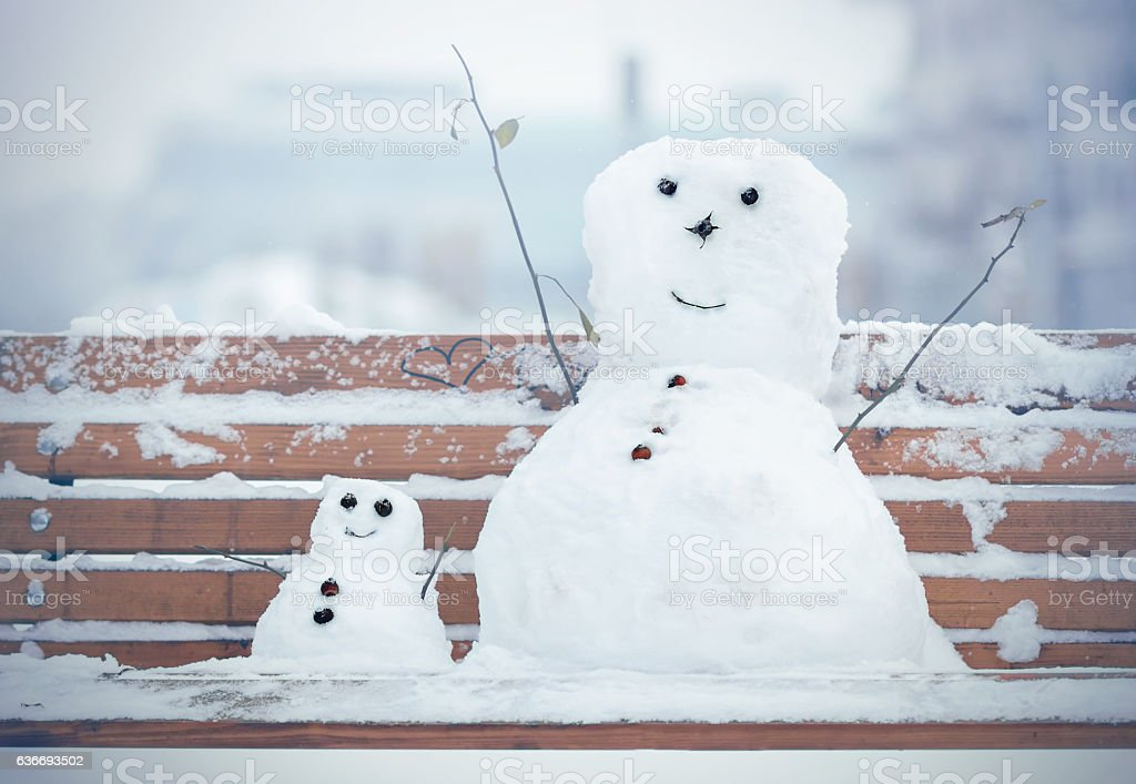 Two Snowman sitting on a bench in a park stock photo