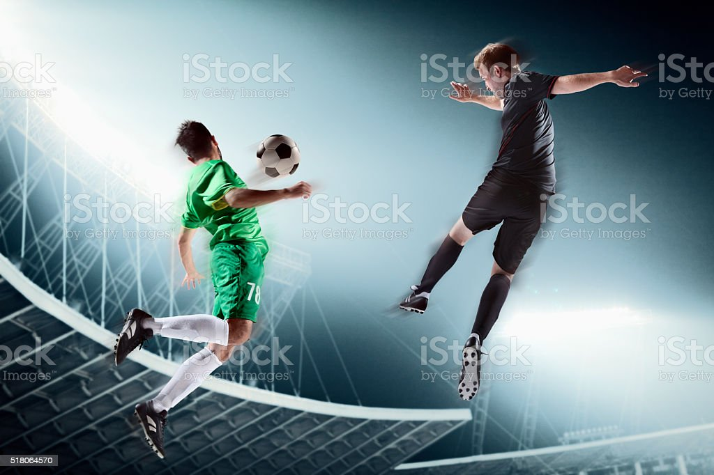 Two soccer players kicking a soccer ball stock photo
