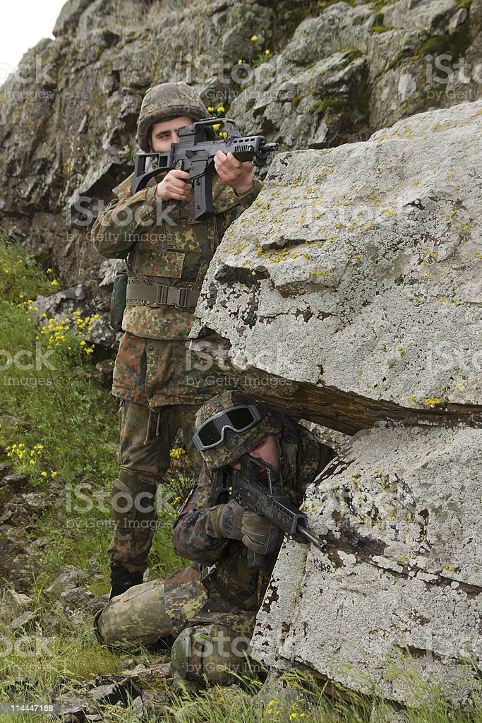 Two soldiers covering behind the rock royalty-free stock photo