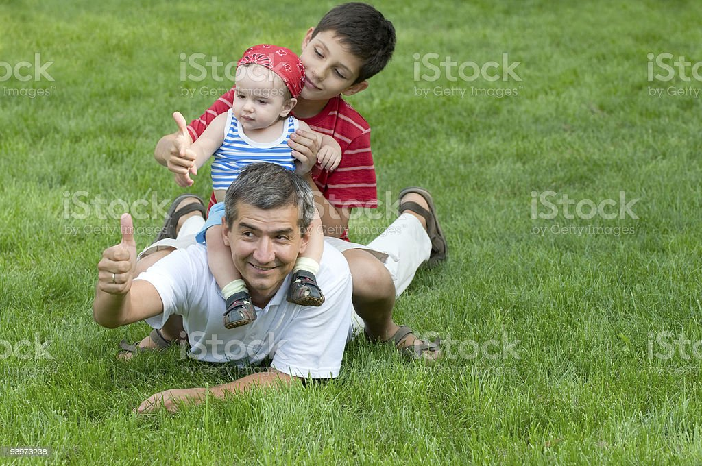 Two sons are sitting on their father's back royalty-free stock photo