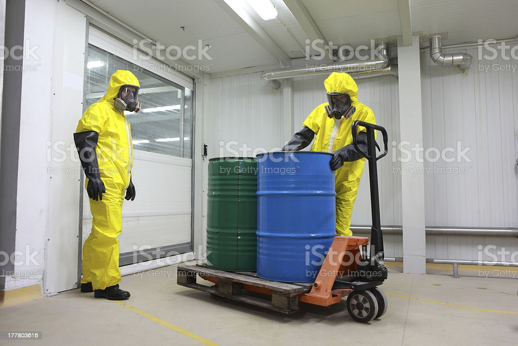 Two specialists dealing with barrels of chemicals royalty-free stock photo