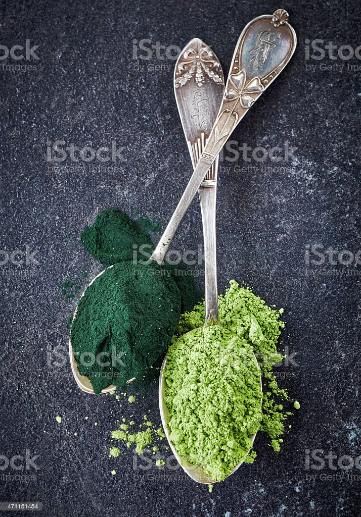 Two spoons of spirulina algae and wheat sprouts powder stock photo