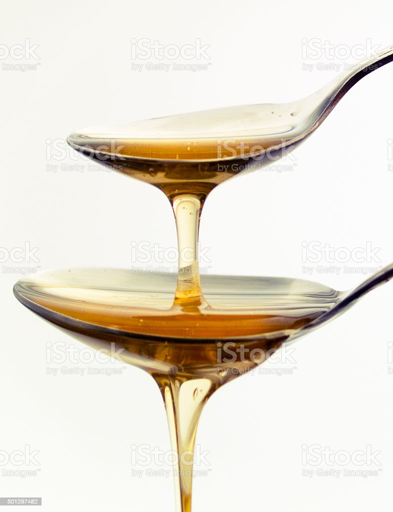 Two spoons with honey stock photo