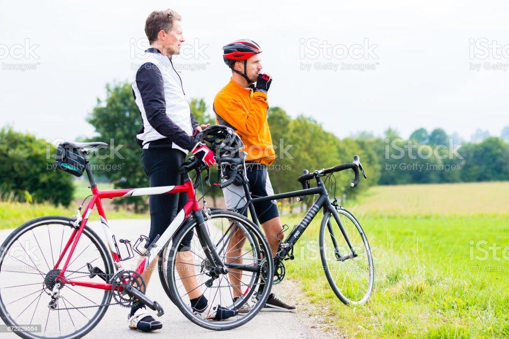 Two sport cyclists having break stock photo
