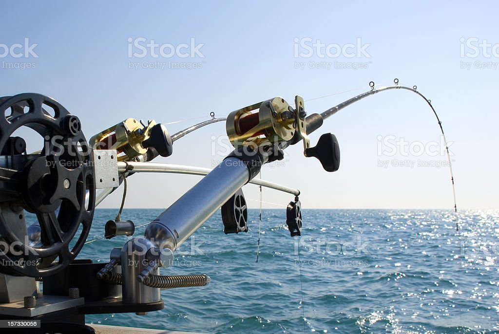 Two Sport Fishing Poles over Turquiose Water stock photo