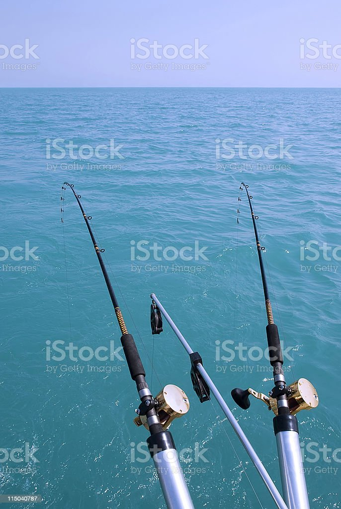 Two Sport Fishing Poles Over Turquoise Water and Blue Sky royalty-free stock photo