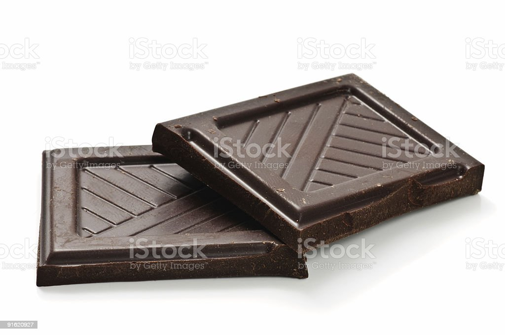 Two squares of dark chocolate on white background stock photo