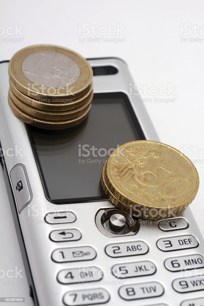 Two staples of euro coins on a silver mobile phone royalty-free stock photo