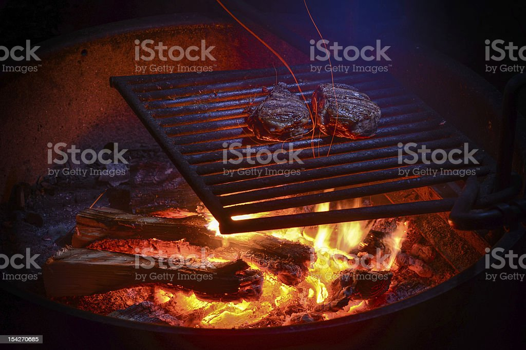 Two steaks grilling on campfire at night royalty-free stock photo