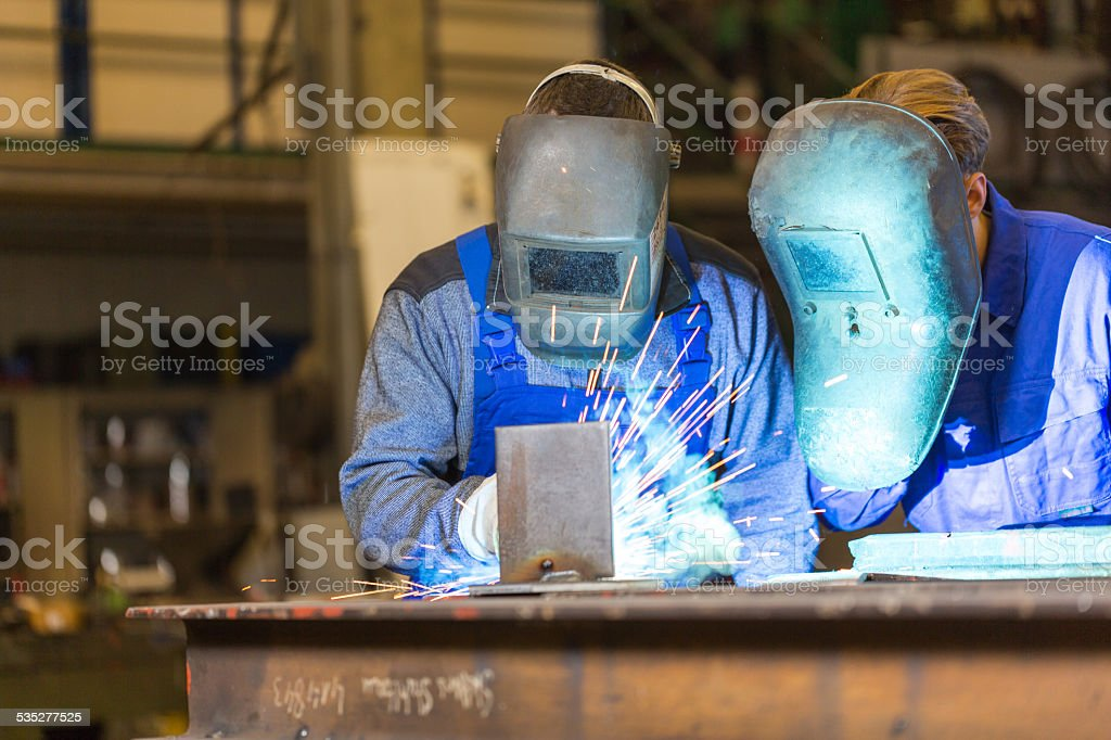 Two steel construction workers welding metal stock photo