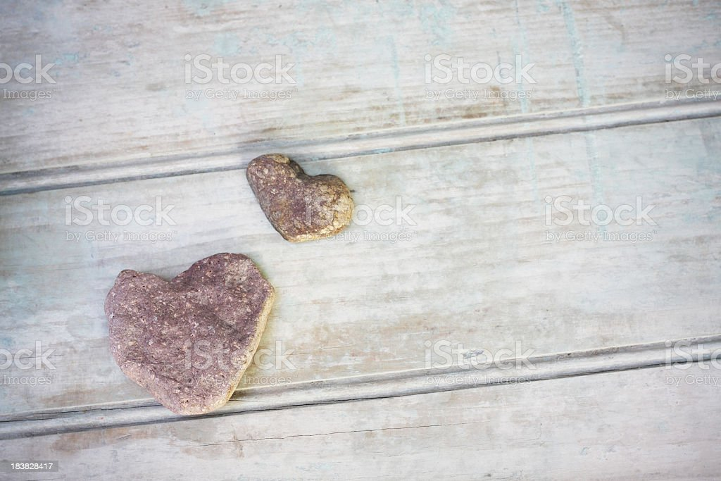 Two stones with heart shape on rustic wood from above royalty-free stock photo