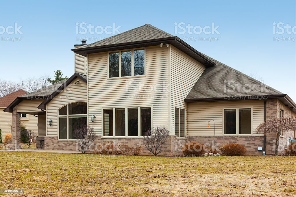 Two Story House With Mixed Brick and Vinyl Siding stock photo