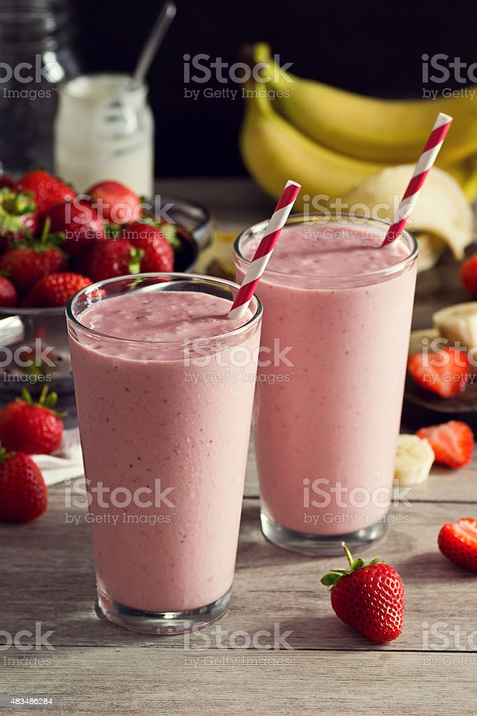 Two Strawberry Banana Yogurt Smoothies in Glasses with Ingredients stock photo