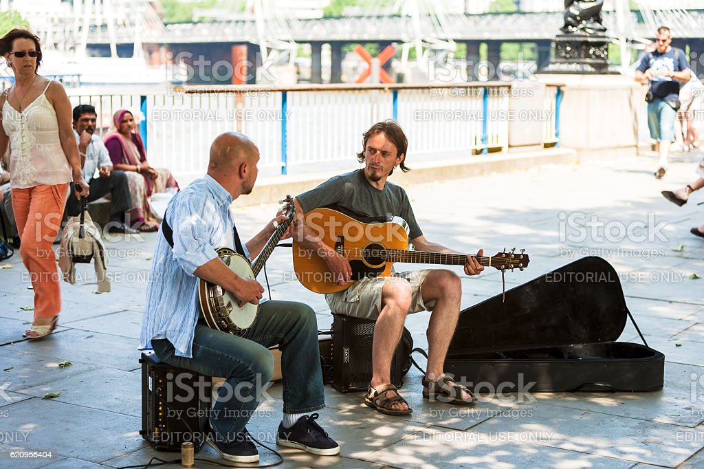 Two street musicians playing on the river embankment. London, UK royalty-free stock photo