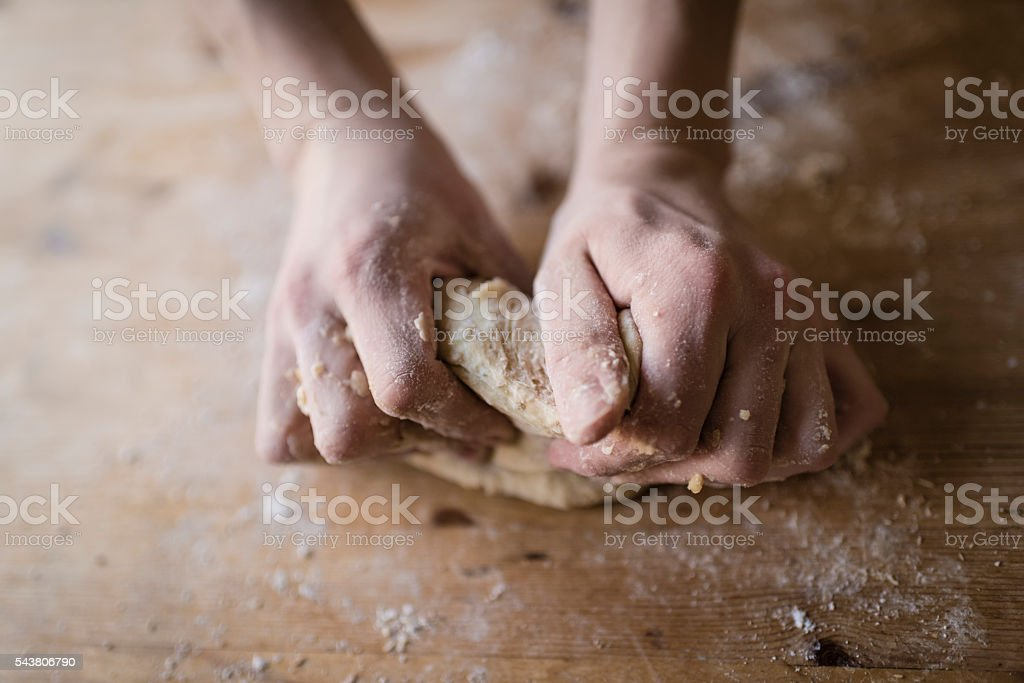 Two strong hands of a baker kneading homemade dough stock photo