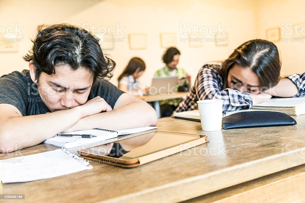 Two students asleep in class after hours of studies stock photo