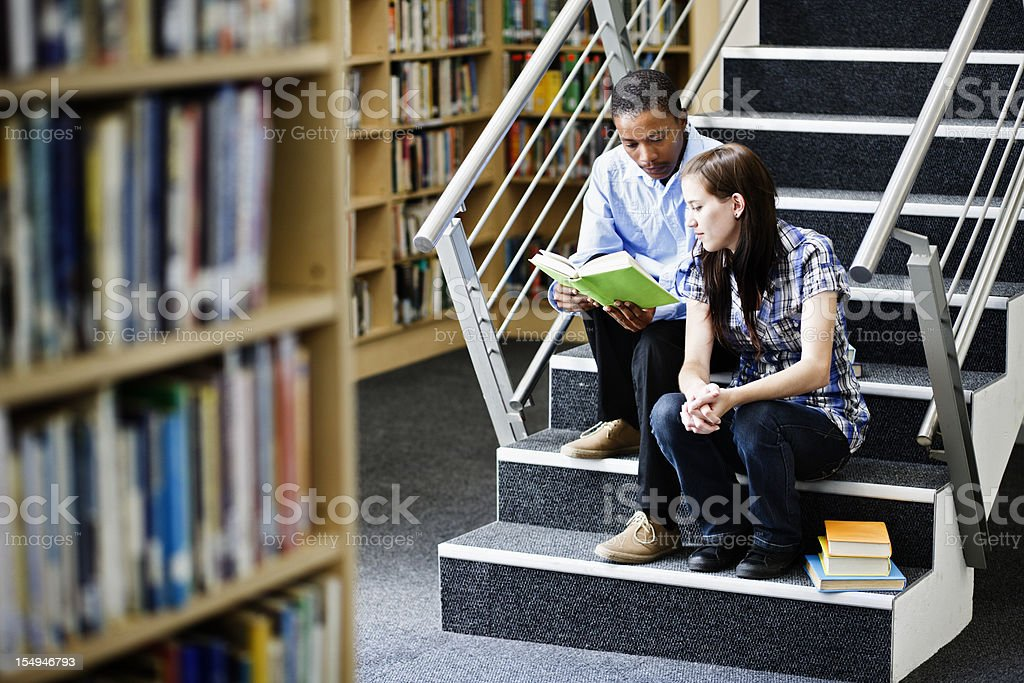 Two students sitting on library steps share a book royalty-free stock photo