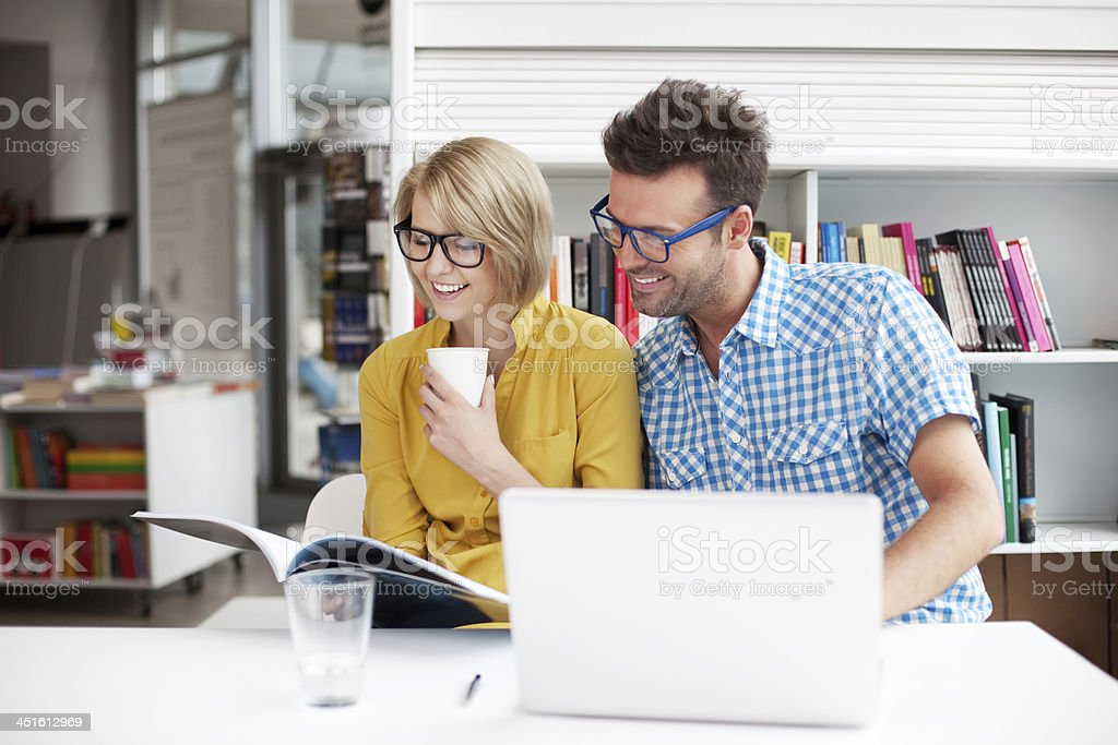Two students studying and smiling in a library stock photo