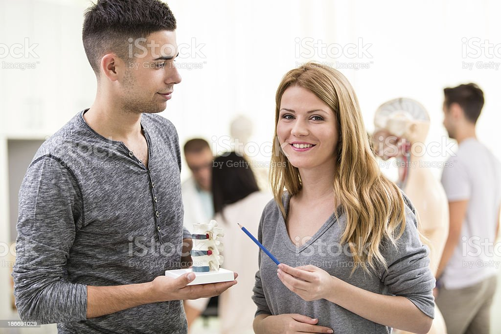 Two students studying human spine stock photo