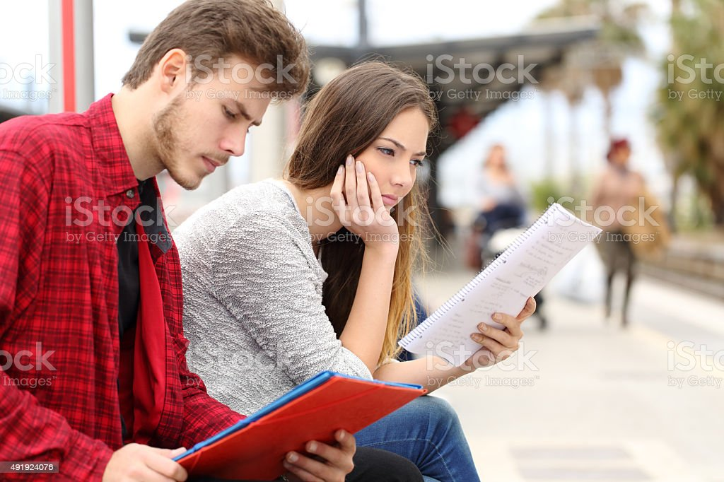 Two students studying waiting transport in a train station stock photo
