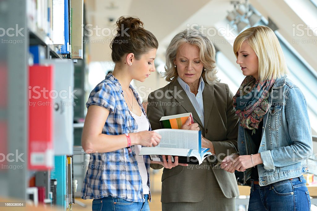 Two Students with their Professor Discussing Book in Library stock photo