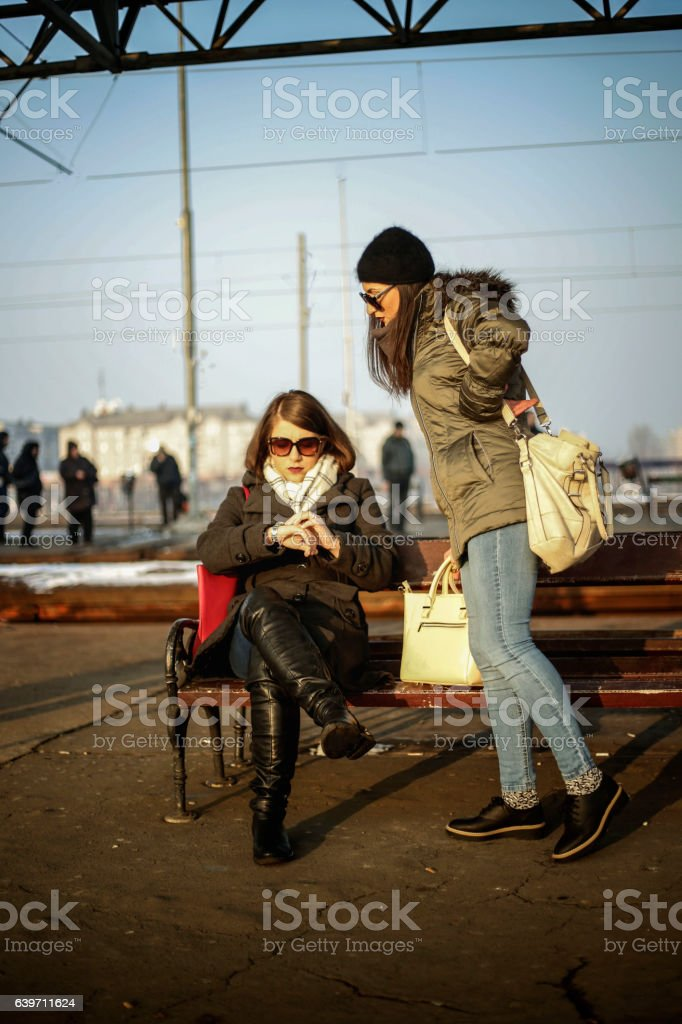 Two stylish young women waiting for a train on station stock photo