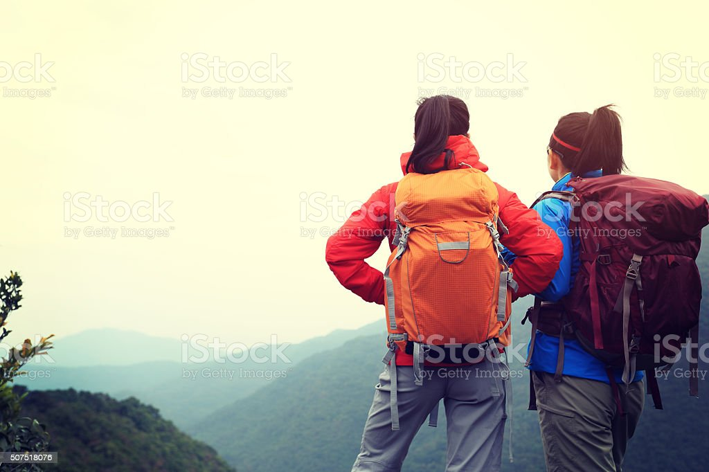 two successful backpacker enjoy the beautiful landscape at mountain peak stock photo