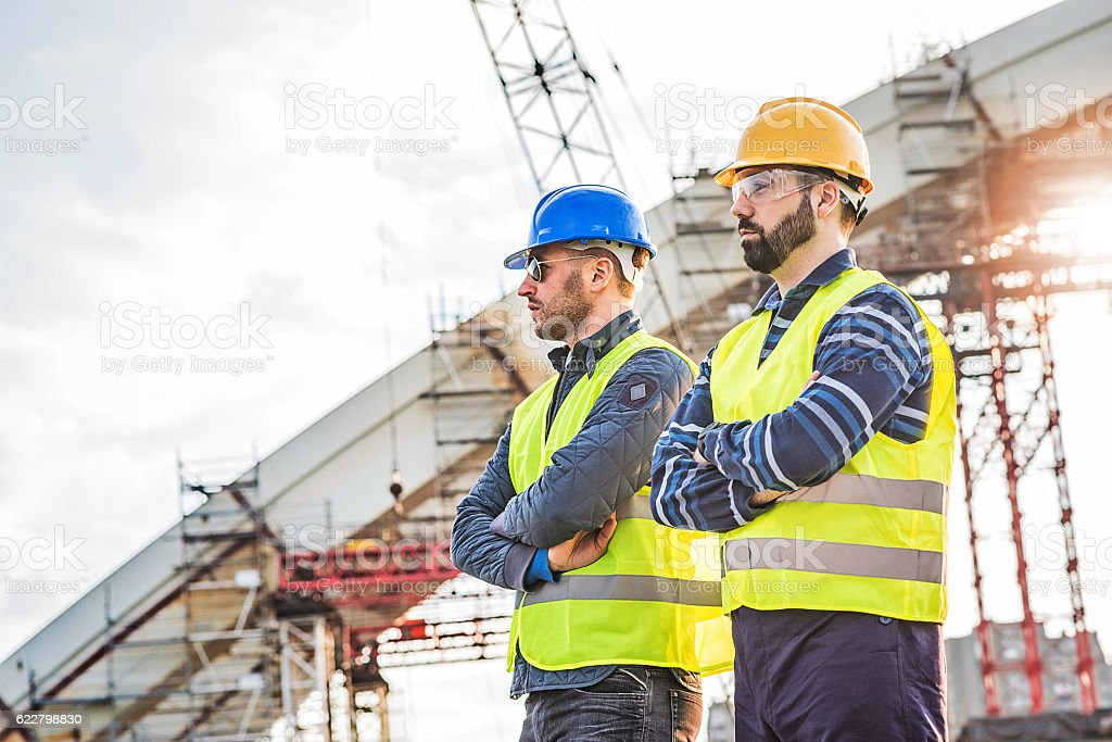 Two successful brdge builders near construction platform with arms crossed stock photo