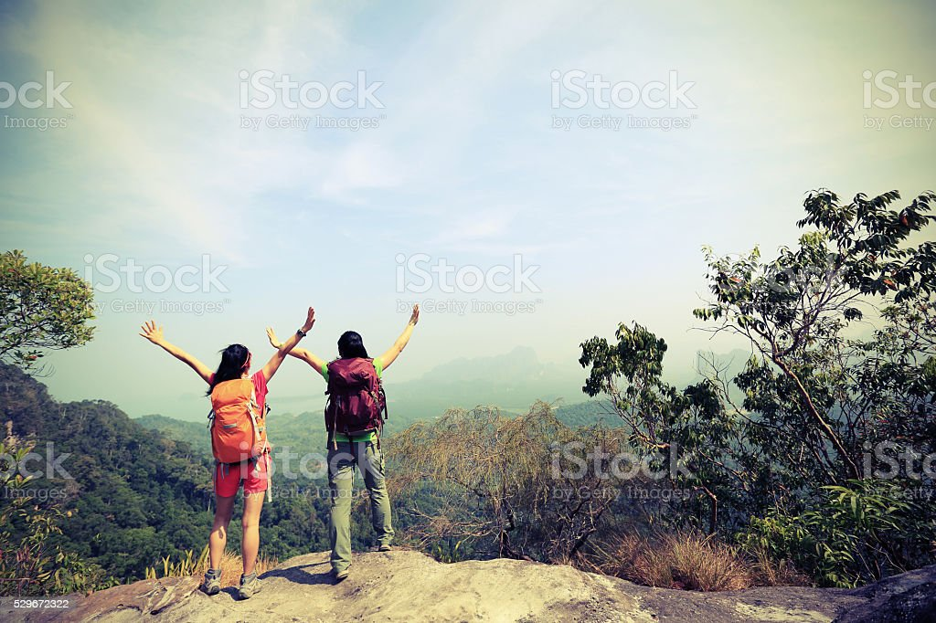 two successful hiking friends enjoy the view on mountain peak stock photo
