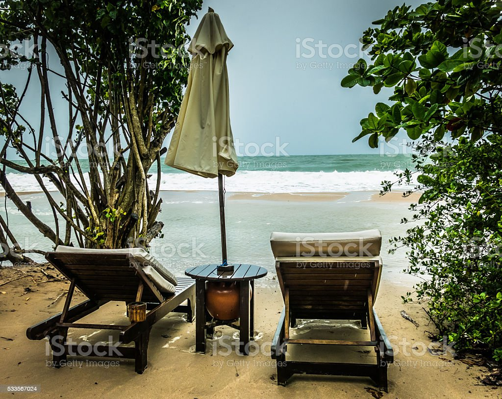 Two Sunloungers and Umbrella at Waters Edge, Krabi, Thailand stock photo