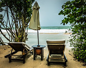 Two Sunloungers and Umbrella at Waters Edge, Krabi, Thailand