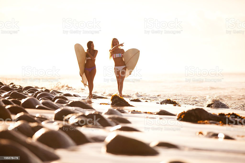 Two surfer girls walking and chatting together stock photo