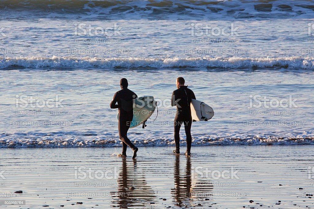 Two surfers entering the water on the Devon coast UK stock photo