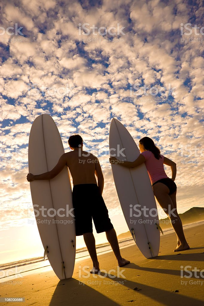 Two Surfers Standing on Beach at Sunrise stock photo